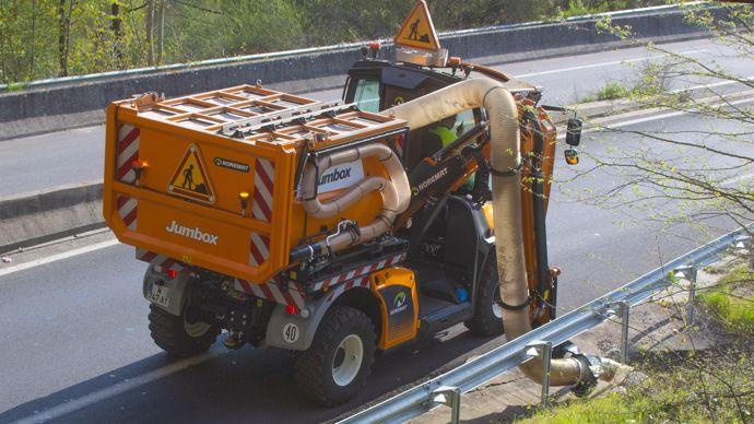 Travaux de ramassage sur le bord d'une route à grande circulation pour le ramassage des déchets.