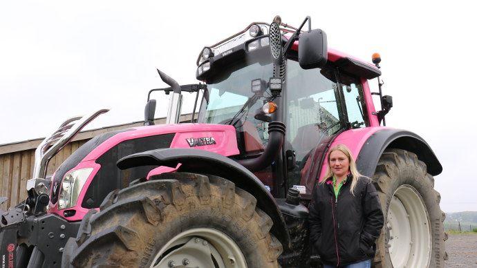Caroline Deveaux devant son tracteur Valtra N163 Rose