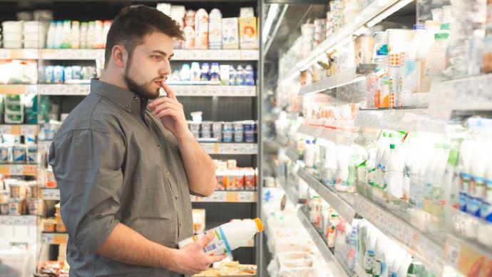 Homme pensif devant le rayon laitier d'un supermarché