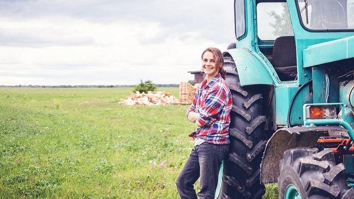 agricultrice devant un tracteur